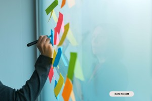 Businesswoman writing on colorful sticky note paper in business office